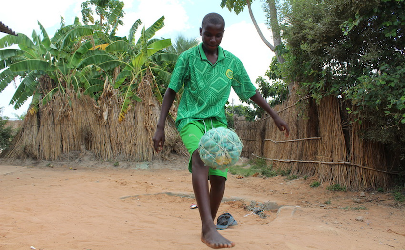 15-year-old boy in green shorts and t-shirt kicks a football (soccer ball) made of twine