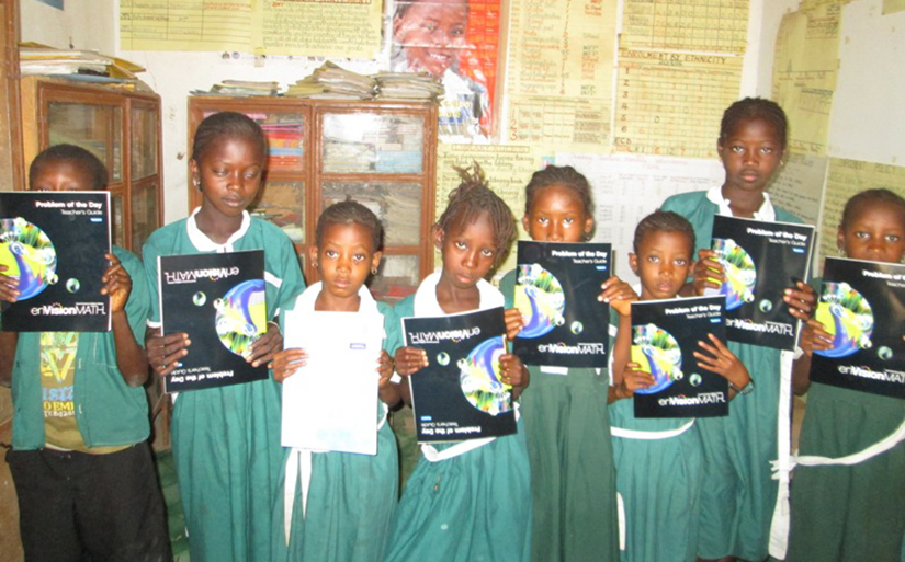 8 Gambian students (1 boy, 7 girls) in green school uniforms holding up books