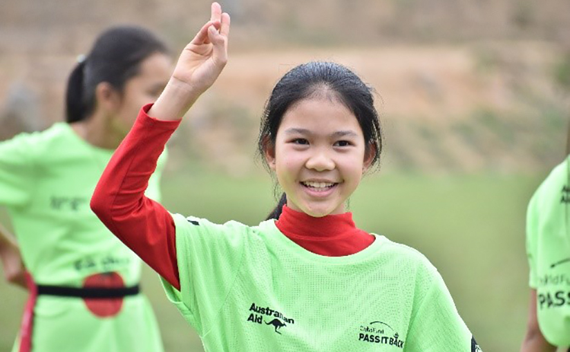 A smiling Vietnamese girl in a green t-shirt over a red shirt holds up her hand in victory