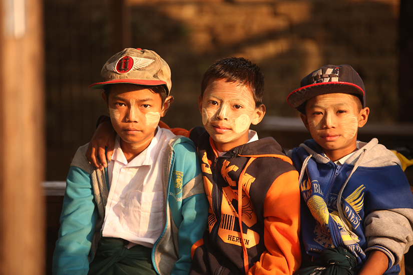 3 boys about 10 years old in Myanmar sit on a bench looking at the viewer.