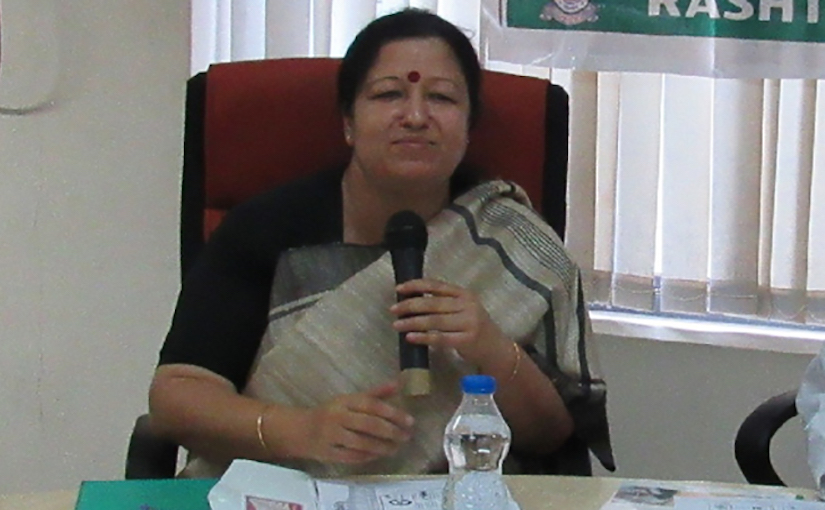 An Indian woman sitting at a table speaks into a microphone