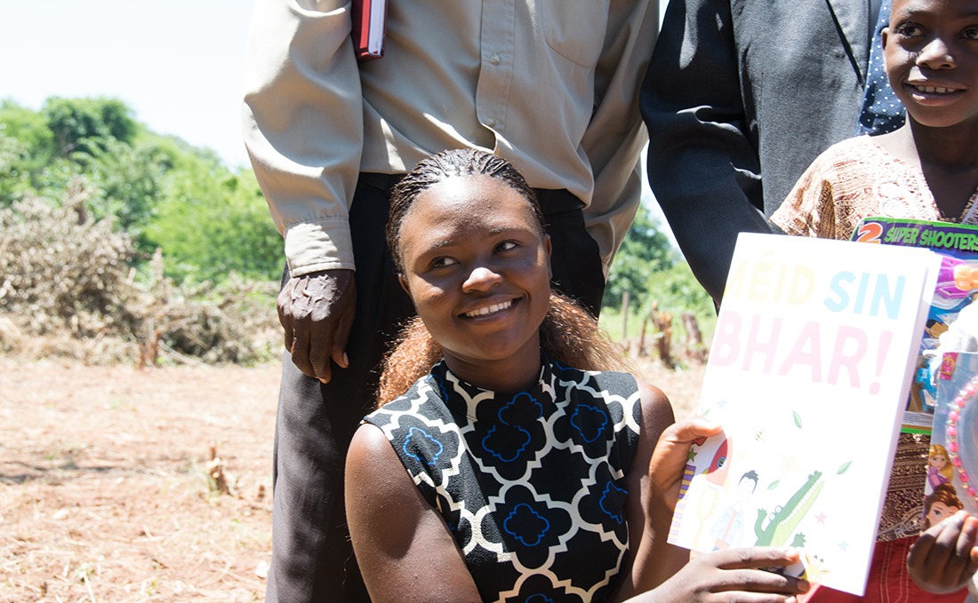 A young Zambian woman holding some school work.