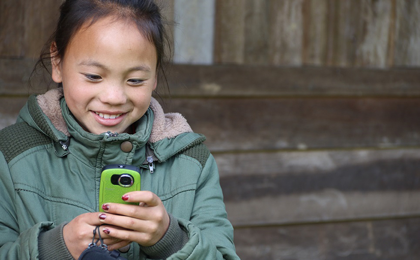 An Asian girl, about 10 years old, in a green jacket looks at her bright green smart phone.