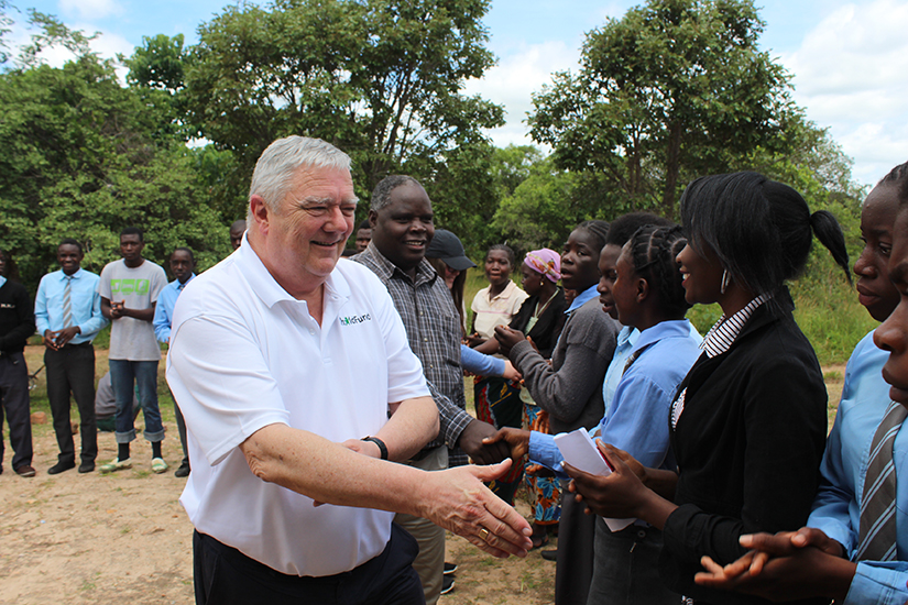 Mick Kiely is shaking hands with a group of African men and women who are standing in a line.