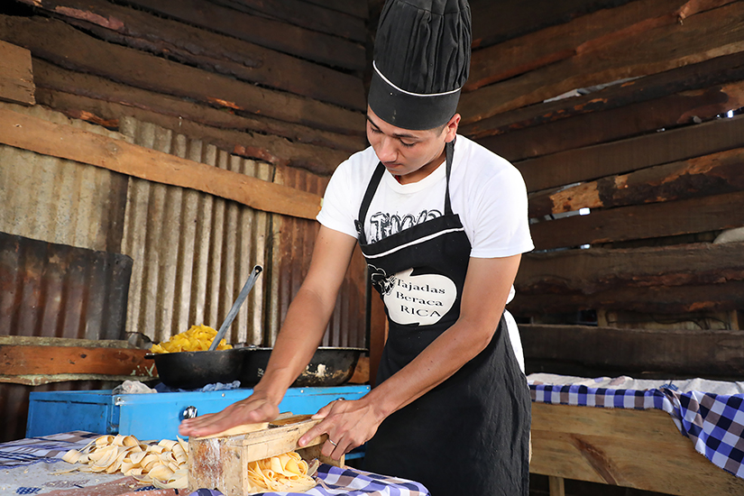 A teenage boy in a white t-shirt, black apron and black baker's hat stands at a table preparing food to sell.