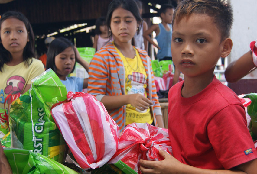 Children receive emergency supplies from ChildFund Alliance member Educo in the aftermath of Typhoon Nock-Ten in the Philippines.