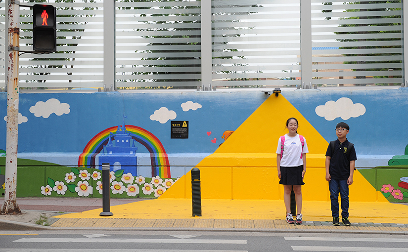 "A girl and a boy student in school uniform stand on a painted yellow triangle that shows drivers where the crosswalk is so the children can cross the road safely. There is a red ""don't walk"" sign above them. There is a mural of a castle and a rainbow behind them."