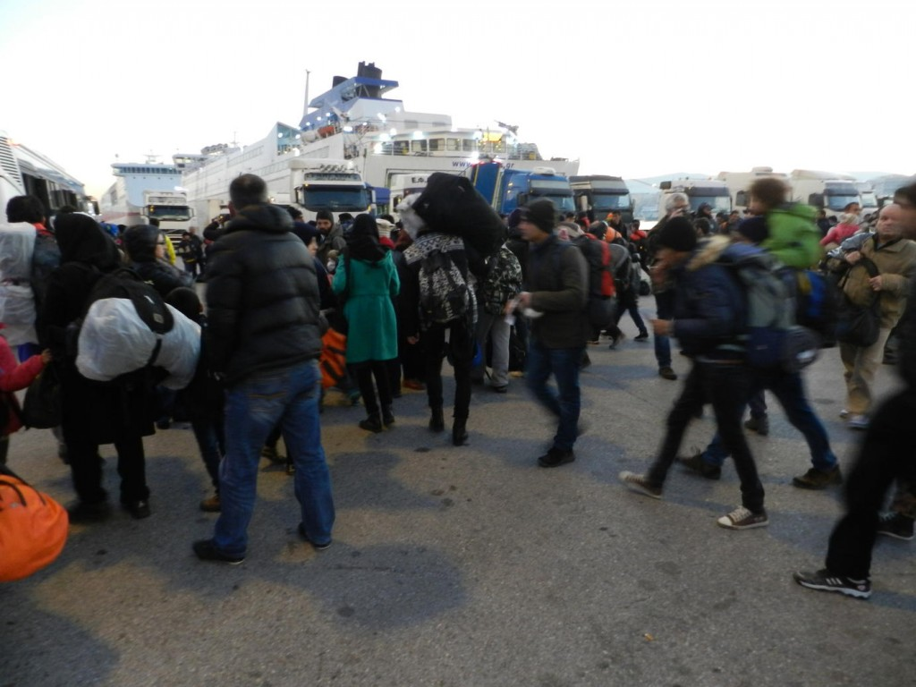 Caption: As dawn breaks, hundreds of migrants spill out from the ferry onto the port of Athens, Greece. As the city wakes up, news has reached the world of yet another migrant boat that didnât make it to Greece. The boat capsized, killing several people, including children. tag = people group standing outdoors boat buses